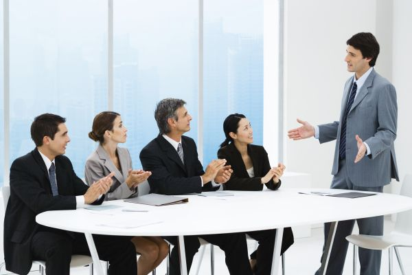 Business people applauding associate's presentation, sitting around table