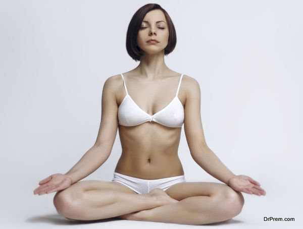 Happy young woman sitting in lotus position
