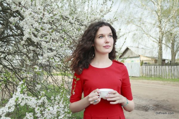 Daydreaming attractive brunette girl at spring fruit tree in white bloom