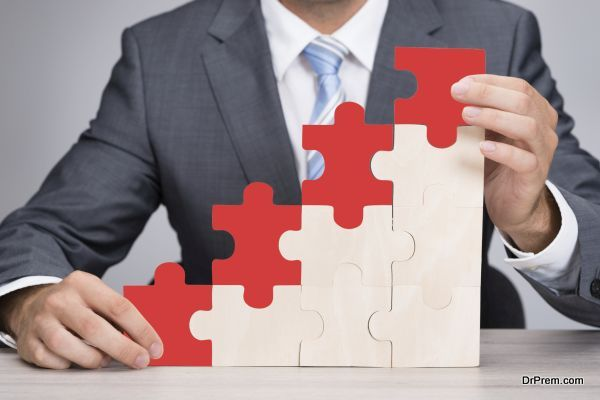 Midsection of businessman holding red jigsaw graph on table against gray background