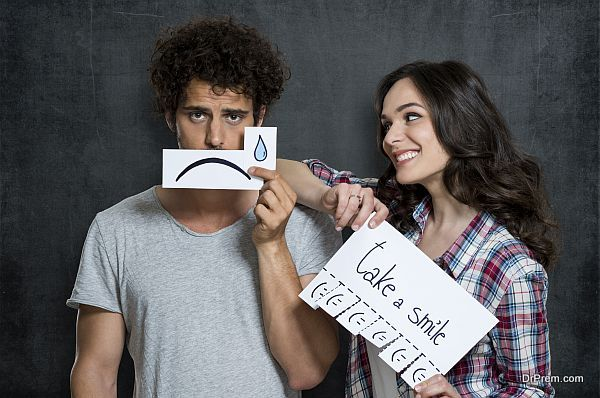 Happy Woman Looking At Man Holding Paper With Tears Drawn On It