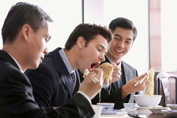 Businessmen eating noodles in restaurant