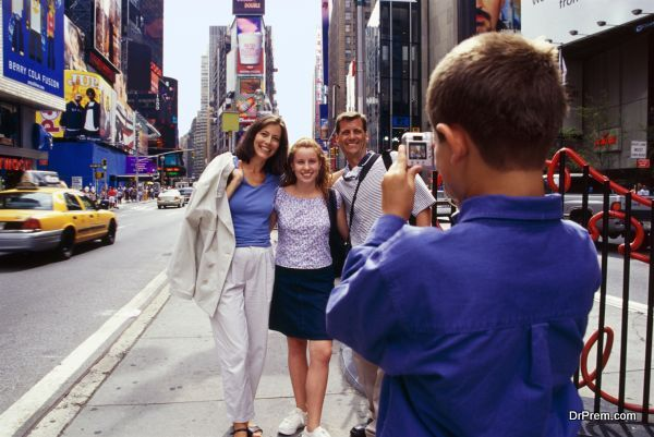 Boy taking photo of family in Times Square