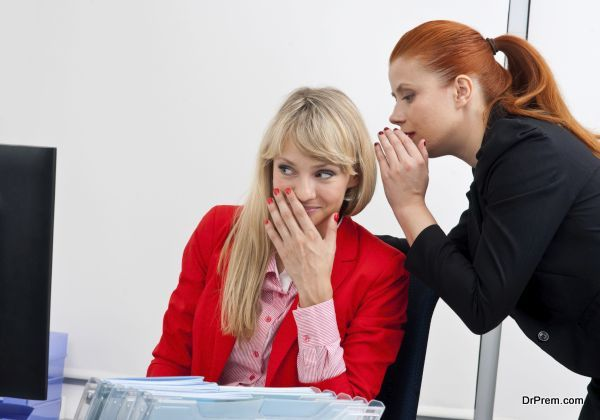 Two attractive business woman colegues gossip in office