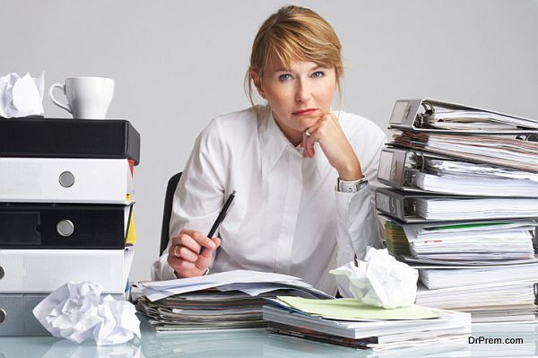 tired businesswoman is sitting at a table full of paperwork