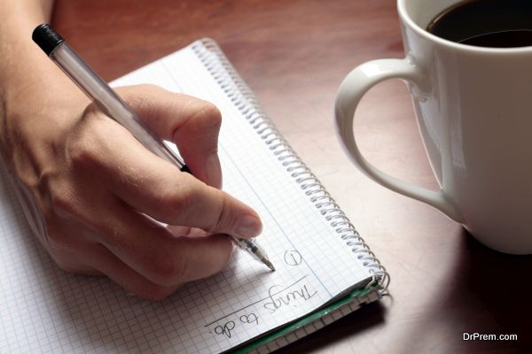 Womans hand with pen, notebook and coffee
