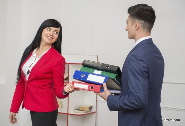 Side view of business man with folders flirting in office with his colleague with pretty smile in red jacket looking at him, with copy space on the wall