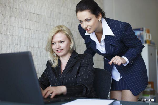 Confident businesswomen team communicate by laptop in office