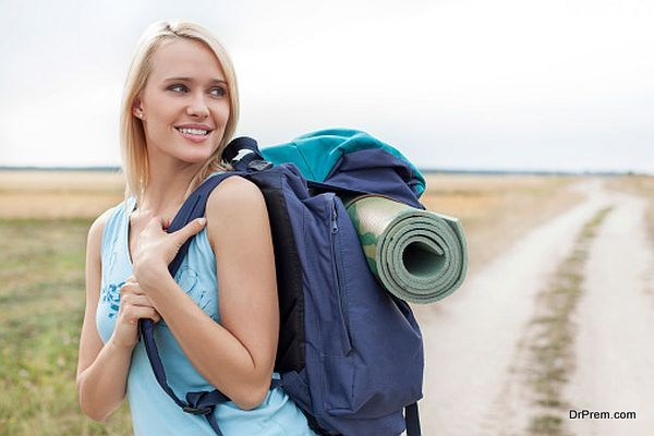 Beautiful woman with backpack looking away while hiking at field