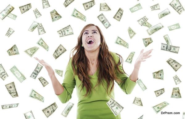Stock image of ecstatic woman trying to catch falling money