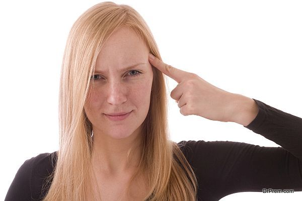 Young woman pointing her finger to her head