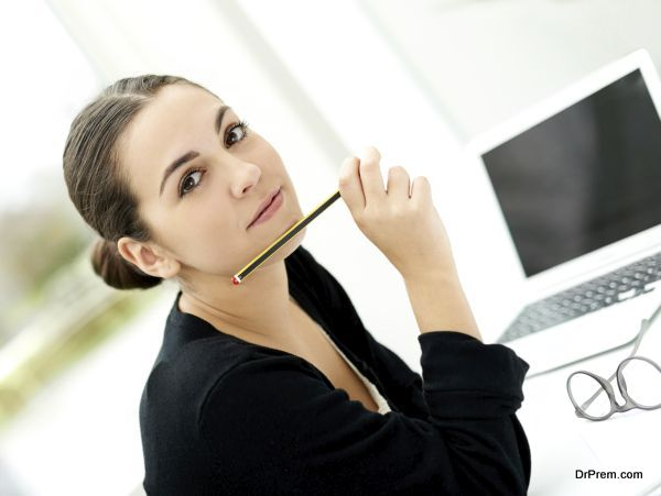 Attractive stylish young businesswoman sitting at her desk with a laptop computer and her pencil raised to her chin looking at the camera with a serious expression