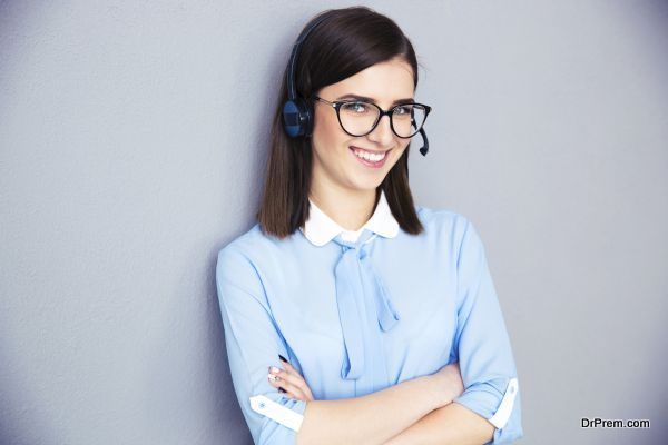 Happy businesswoman with headset and arms folded