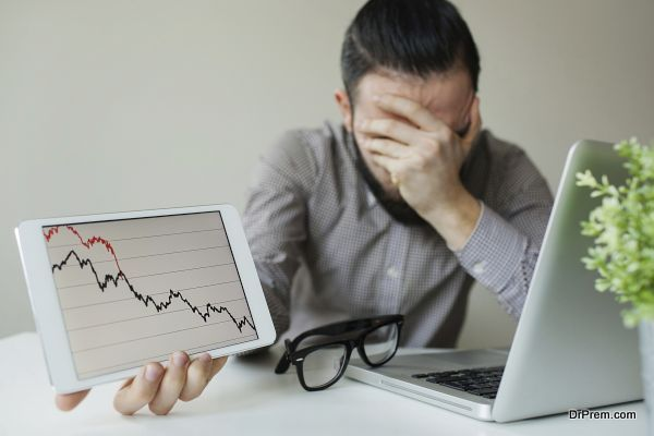 Depressed businessman leaning head below bad stock market chart
