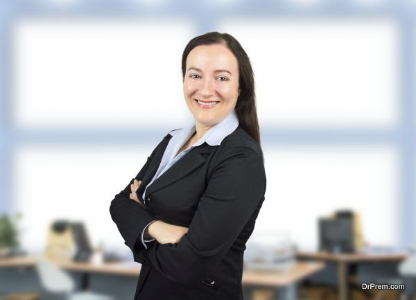 Portrait of a businesswoman standing at the office with arms crossed and smiling
