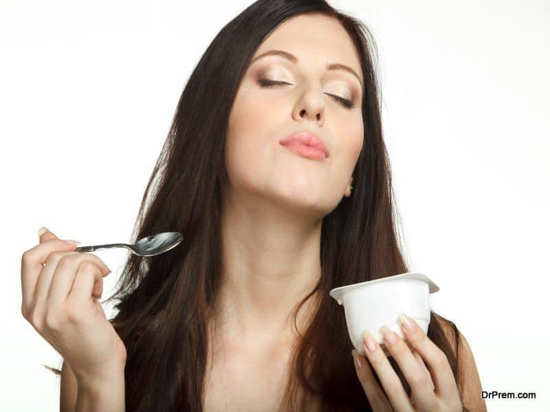 Brown haired young woman enjoying yogurt with spoon