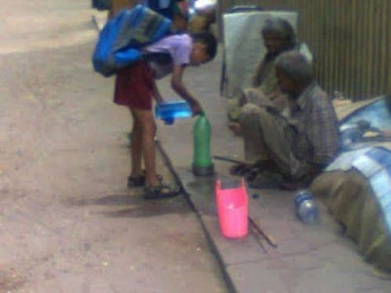 A school boy gives water to the thirsty homeless man