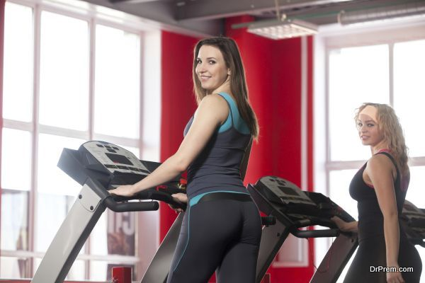 Two sporty girls walk on treadmill