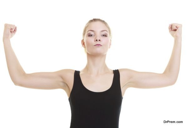 Fitness woman showing energy flexing biceps