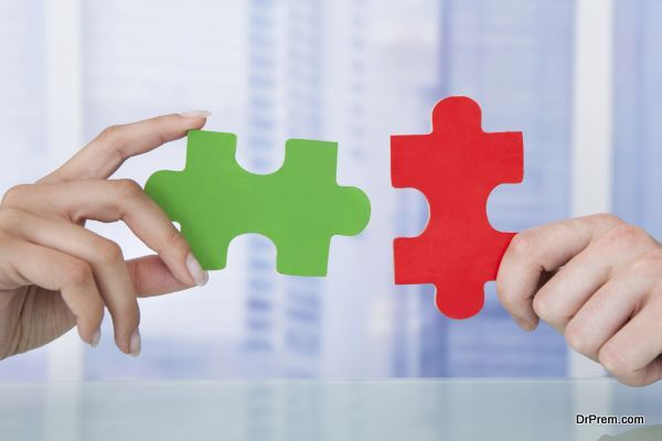 Cropped image of business people joining jigsaw pieces in office