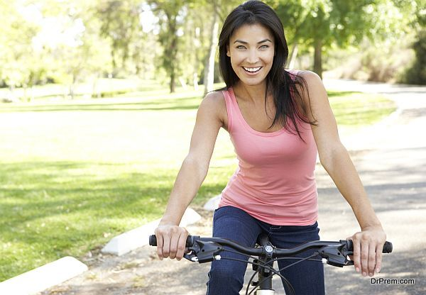 Young Woman Riding Bike In Park