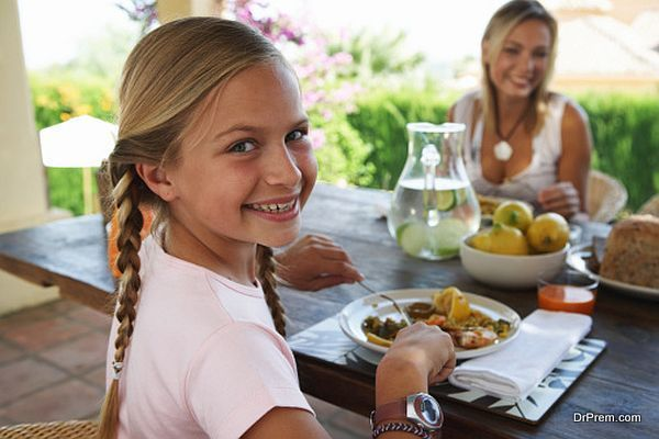 Mother and daughter (10-12) eating at table (focus on girl smiling)