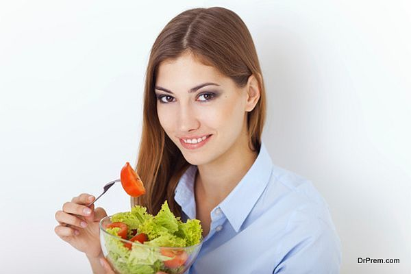 happy young woman eating a fresh salad