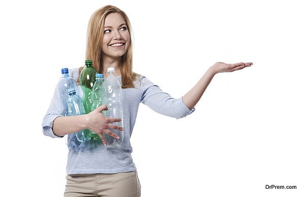 Female environmentalist with plastic bottles showing on copy space