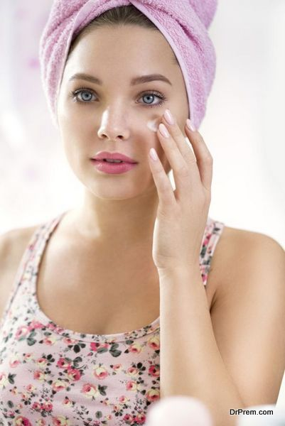 Young girl applying cream on face , skincare