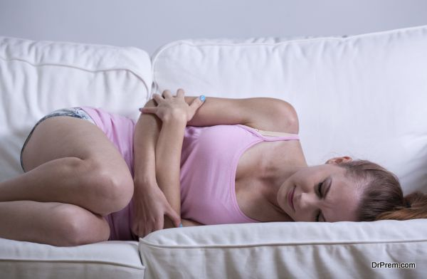 Young girl curled up on the couch having abdominal cramps