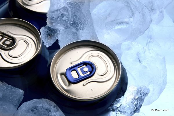 Three aluminium cans of beer and ice