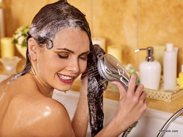 Woman washes her head at home bathroom. Wetting hair.