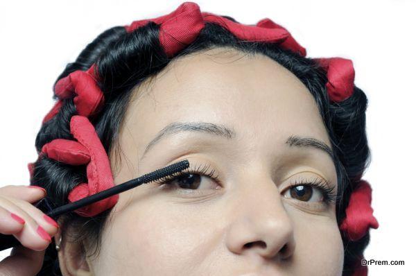 Young Indian girl applying mascara on eyelashes.