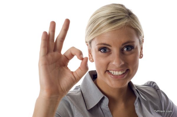 Smiling business woman showing okay sign isolated over a white background
