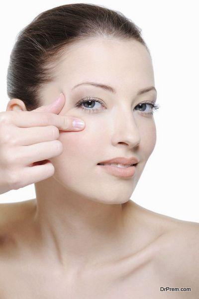 portrait of young woman doing crease near her eye - studio