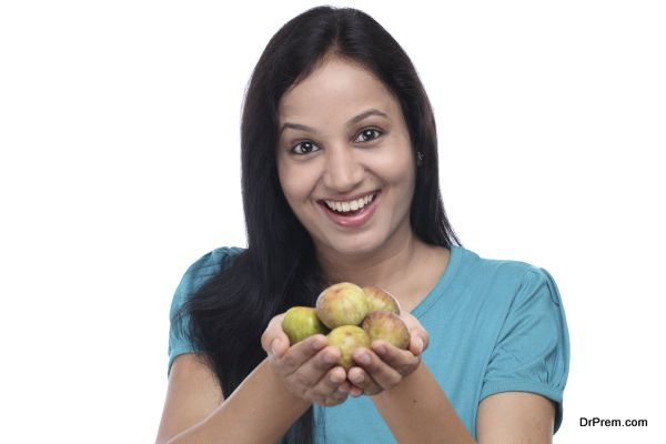 Young woman holding fig fruit in her hands against white background