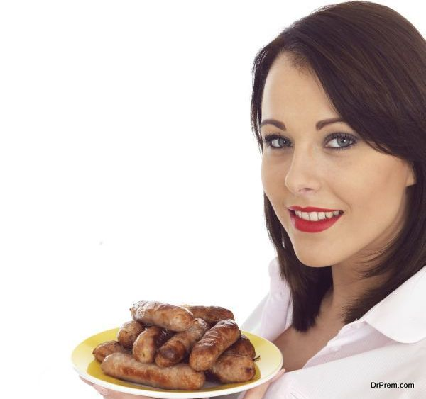 Young Woman Holding a Plate of Pork Sausages