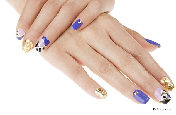 Nail art with gold colors and studs. Stylish geometric pattern.