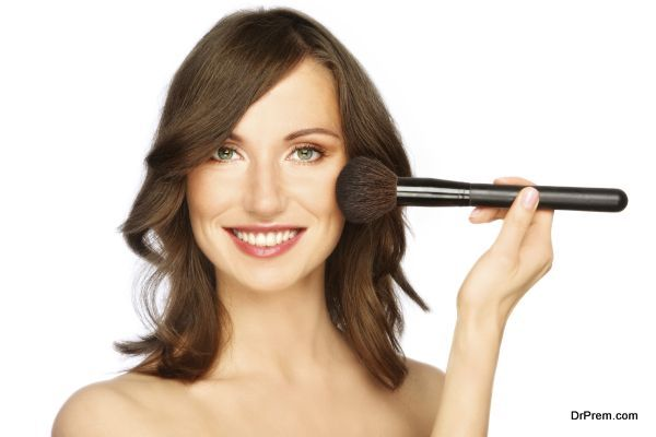 Beautiful happy smiling young woman applying make-up with big brush, on white background