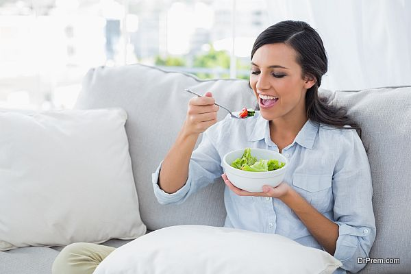 Happy woman relaxing on the sofa eating salad