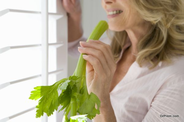 woman holding celery stick, standing by window, smiling, side vi