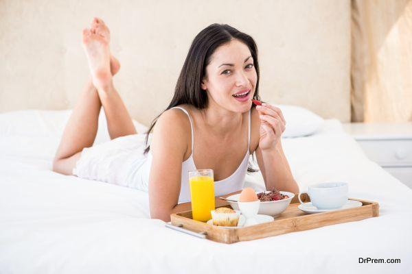 Pretty brunette eating her breakfast on bed