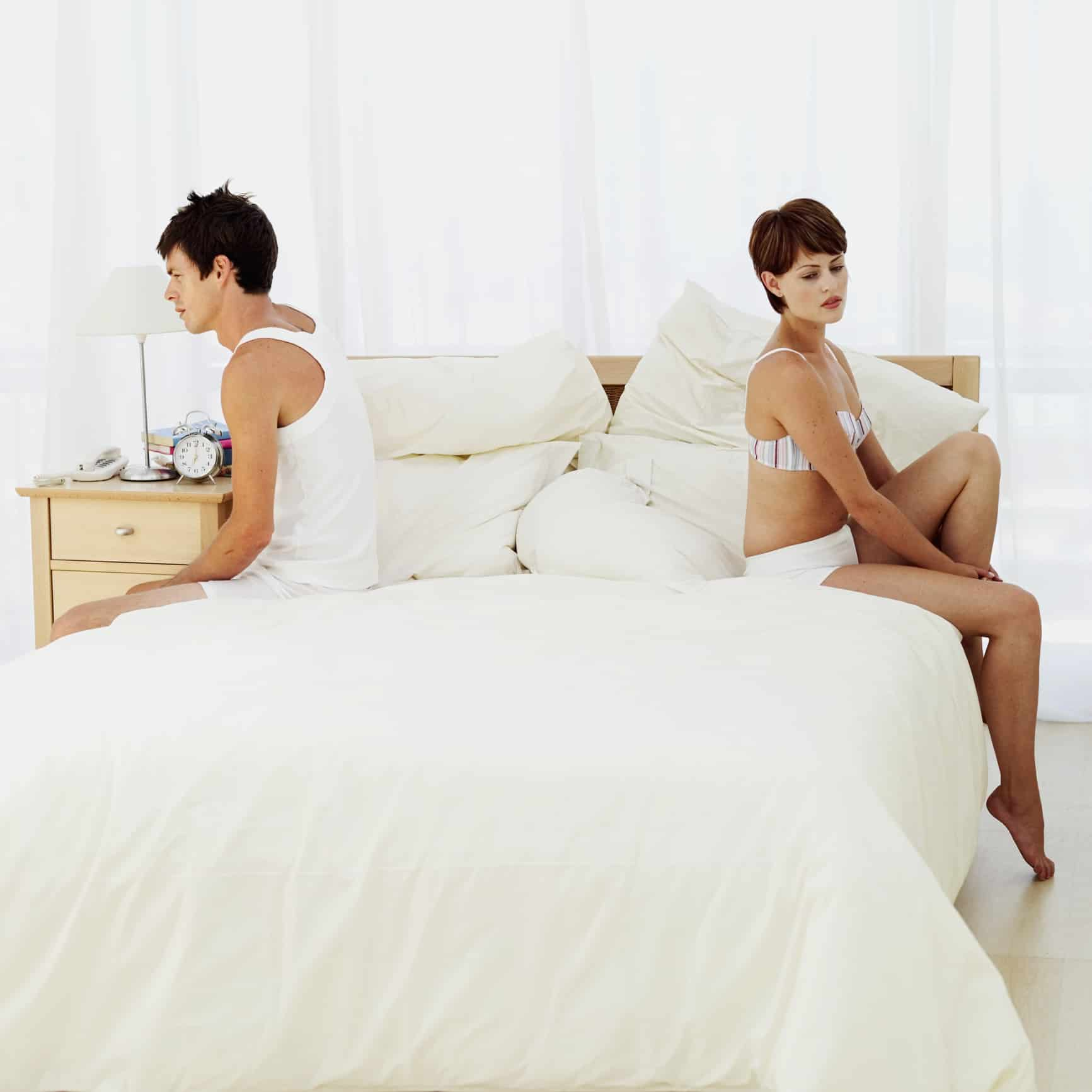 side profile of a young couple sitting back to back on the bed