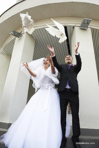 Joyful Bride and groom release pigeons