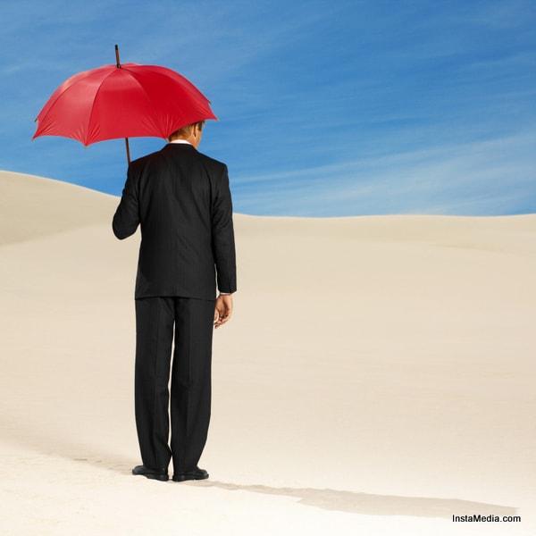 rear view of a man standing holding an umbrella