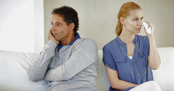 Portrait of angry couple with problems sitting on sofa