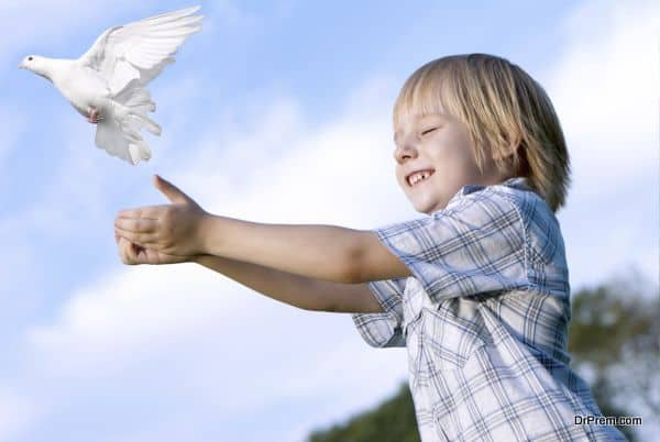 Little boy releasing a white pigeon in the sky