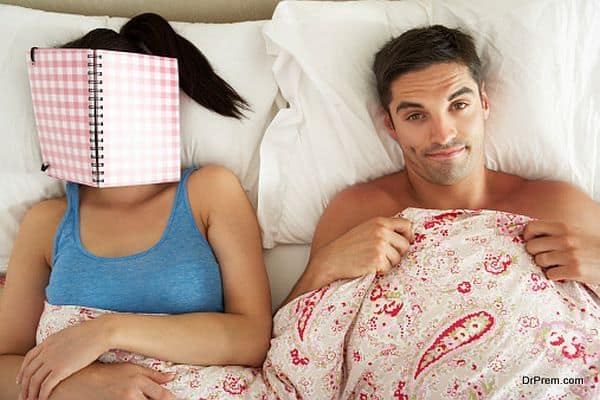 Bored Looking Man Lying In Bed Next To Woman Reading Book