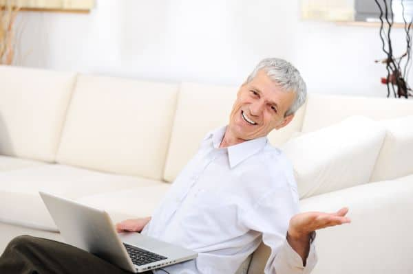 relaxed senior man with laptop on sofa smiling