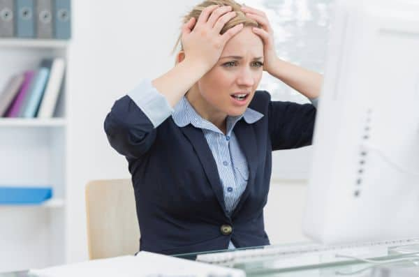 Frustrated business woman sitting with head in hands in front of computer at office desk